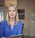 Woman sitting in office using digital tablet - RHF001547