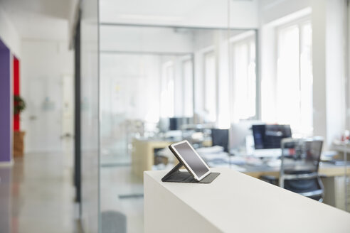 Interior of bright modern office with digital tablet on ledger - RHF001589