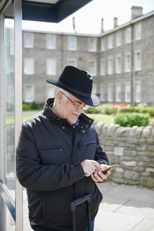 UK, Bristol, senior man using  smartphone while waiting at bus stop - JCF000007