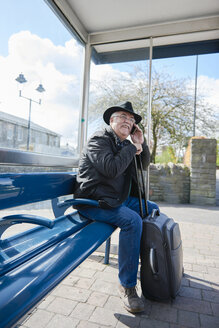 UK, Bristol, portrait of smiling senior man telephoning with smartphone while waiting at bus stop - JCF000010