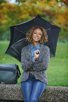 Portrait of smiling woman with umbrella - JCF000023