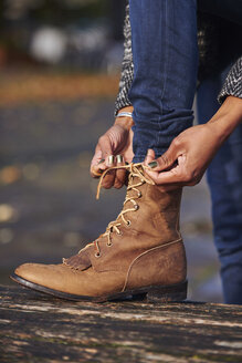 Hands of woman tying boot - JCF000029