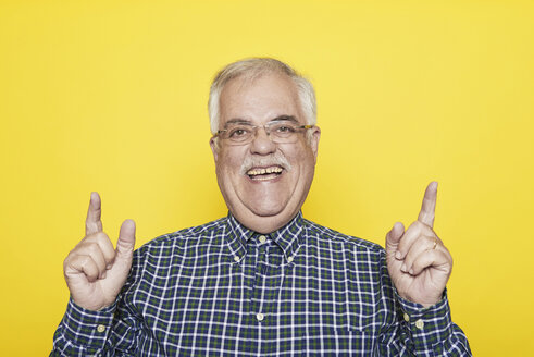 Portrait of laughing senior man gesturing in front of yellow background - JCF000030