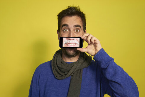 Portrait of man holding smartphone with photography of another man's smiling mouth - JCF000033