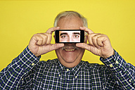 Portrait of smiling senior man holding smartphone with photography of another man's eyes - JCF000036