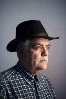 Portrait of serious senior man wearing black hat in front of grey background - JCF000042