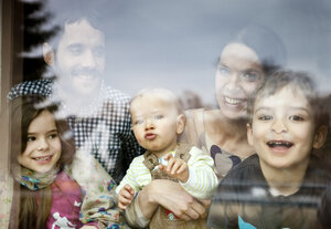 Happy family of five looking through window pane - MFF002975