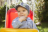 Portrait of toddler sitting in plastic swing - MFF002993