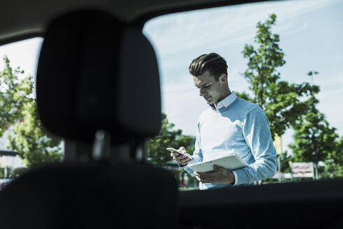 Young man with cell phone outside car - UUF007478