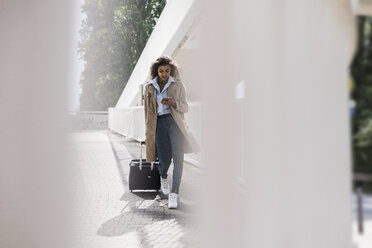 Young woman with luggage and cell phone on the move - UUF007511