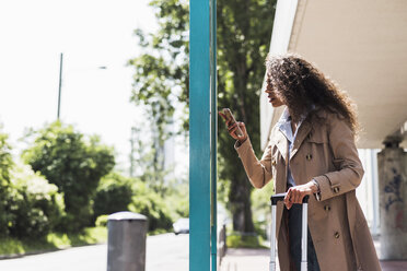 Young woman with luggage and cell phone at bus stop - UUF007514