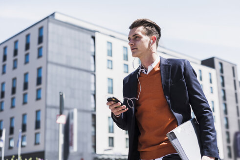 Young man with cell phone, earbuds and folder on the move - UUF007526