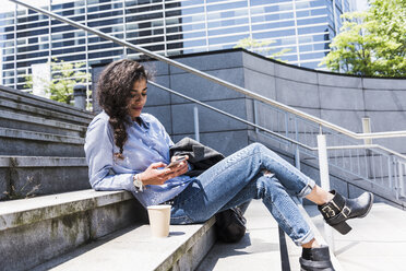 Young woman sitting on stairs looking at cell phone - UUF007532
