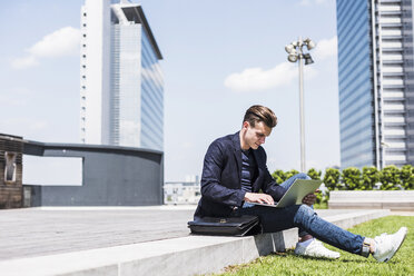 Young man sitting outdoors using laptop - UUF007550