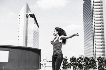 Enthusiastic young woman with outstretched arms outdoors - UUF007556