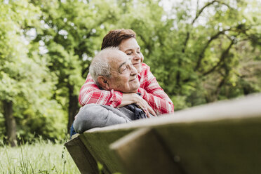 Happy woman hugging her old father sitting on a bench in nature - UUF007569