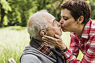 Woman kissing her old father sitting on a bench in nature - UUF007575