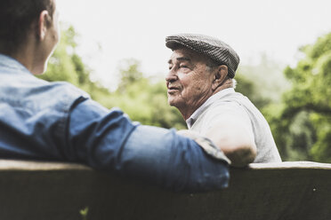 Portrait of senior man talking with his grandson on a bench - UUF007599