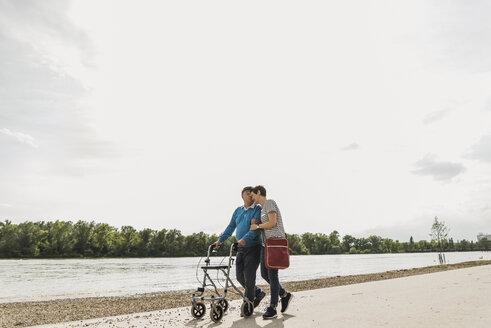 Senior man strolling with daughter at riverside - UUF007605