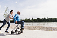 Woman pushing her old father sitting on wheeled walker - UUF007620