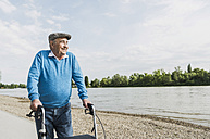 Smiling senior man strolling with wheeled walker at riverside - UUF007623