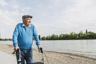 Smiling senior man strolling with wheeled walker at riverside - UUF007623