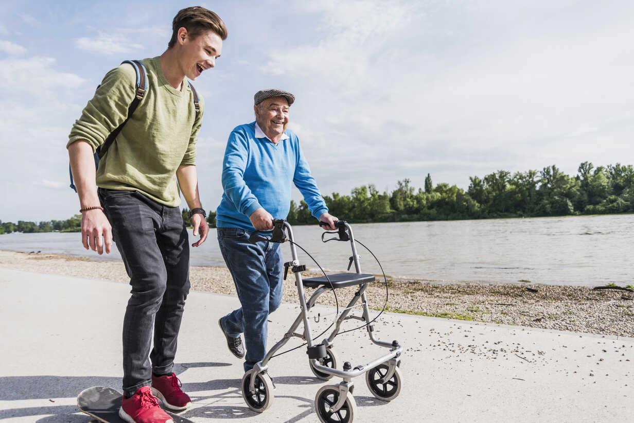 Grandfather and grandson strolling together at riverside - UUF007626 - Uwe Umstätter/Westend61