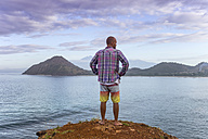 Indonesia, Sumbawa island, Young man standing on viewpoint - KNTF000299