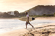 Indonesia, Sumbawa island, Surfer on a beach in the evening - KNTF000311
