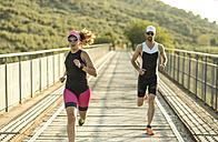 Two athletes running on a bridge - JASF000736