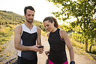 Sportive man and woman looking at smartphone in rural landscape - JASF000745