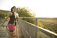 Sportive man and woman stretching on a bridge at sunset - JASF000748
