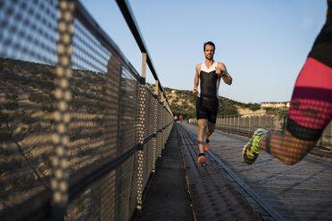 Two athletes running on a bridge - JASF000751