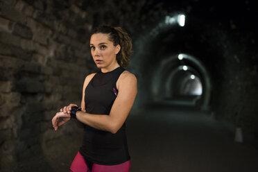 Sportive woman using smartwatch in a tunnel - JASF000754