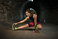 Sportive woman stretching in a tunnel - JASF000757