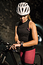 Sportive woman with bicycle looking at smartwatch in a tunnel - JASF000760