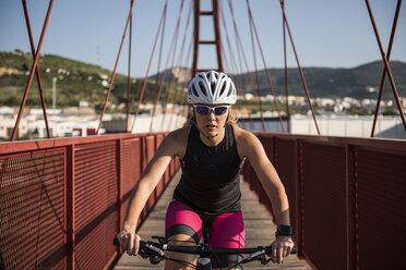 Athlete riding bicycle on a bridge - JASF000766