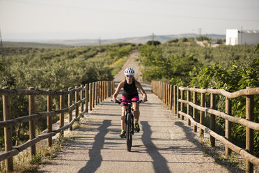 Athlete riding bicycle in rural landscape - JASF000769