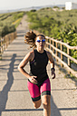 Athlete running in rural landscape - JASF000772