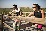Sportive man and woman stretching on a bridge - JASF000775