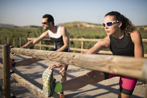 Sportive man and woman stretching on a bridge - JASF000775
