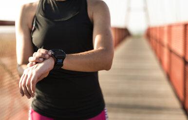 Sportive woman looking at smartwatch on a bridge - JASF000778