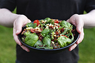 Hands holding bowl with prepared rice salad - EVGF002969