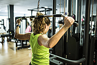 Woman training back with pull machine - JASF000783