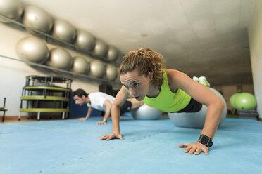 Woman doing pushups in gym - JASF000789