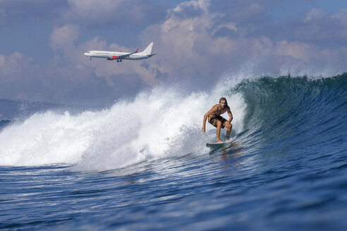 Indonesia, Bali, Surfer on wave, airplane in the background - KNTF000320