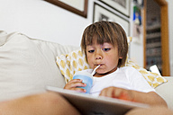 Litte boy sitting on couch using digital tablet while drinking something - VABF000528