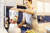 Young woman in kitchen preparing a healthy drink in blender - JRFF000734