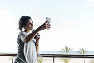 Young woman with healthy drink taking selfie on balcony - JRFF000743