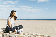 Young woman with healthy drink sitting on wall at the beach - JRFF000746